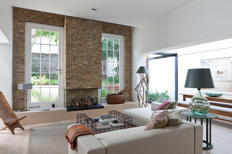 Eclectic living room with a brilliant fireplace and brick backdrop