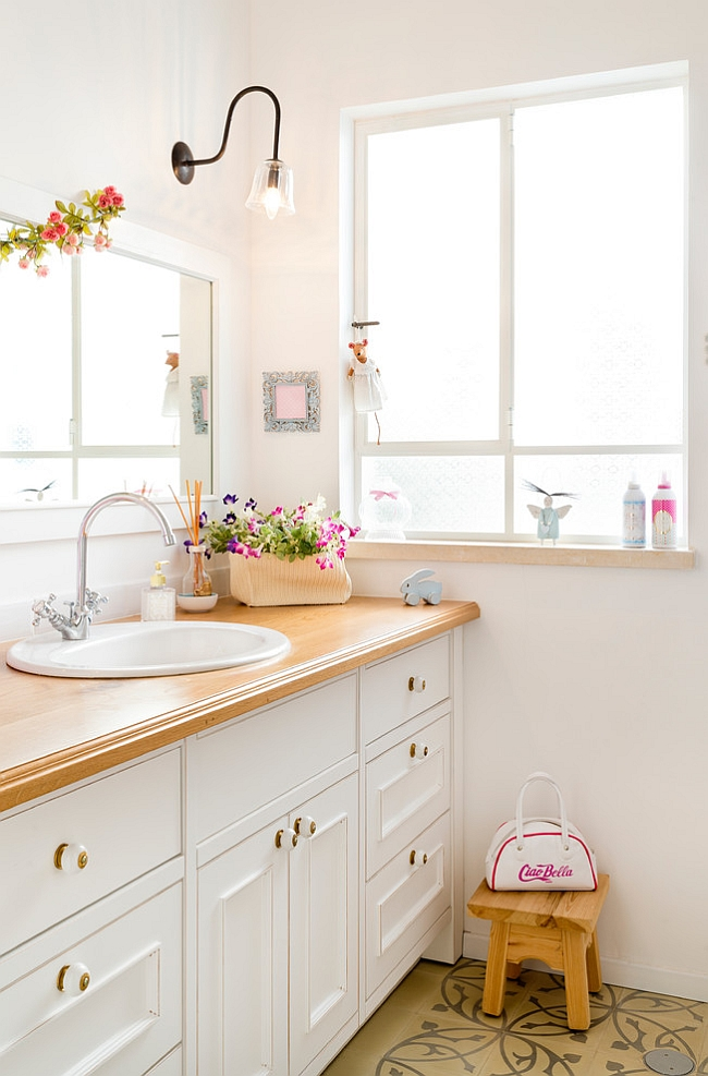 Flowers bring a touch of feminine charm to the eclectic bathroom [Design: Davidie Rozin Architects]