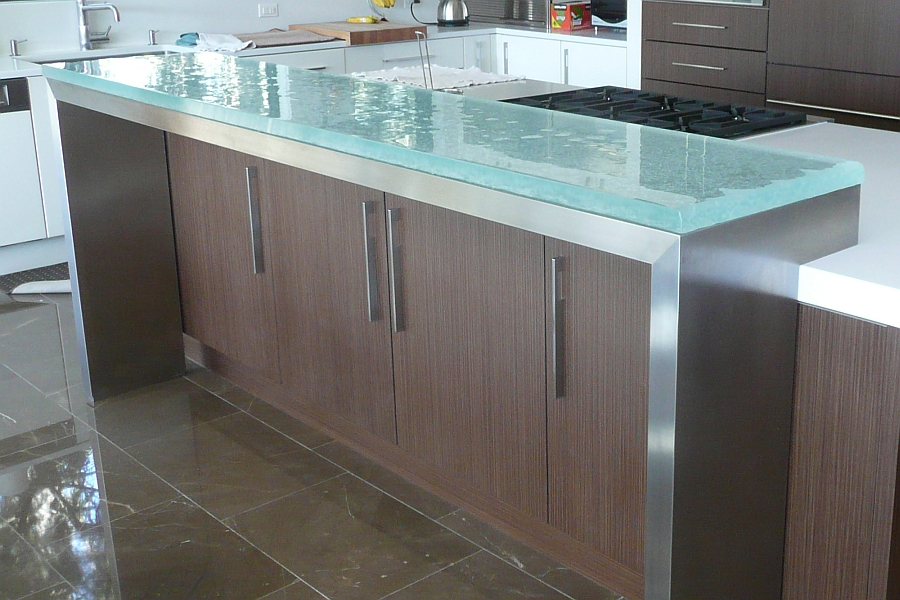 Glass countertops add instant sheen to the stylish kitchen