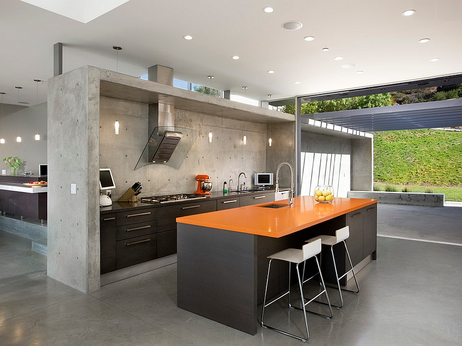 Industrial kitchen with an orange quartz countertop and dark island [Design: Abramson Teiger Architects]