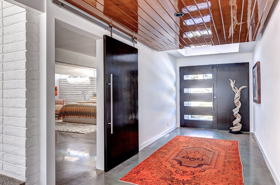 Large barn door used to separate the master suite from the gorgeous entry with pops of red Two Story Mid Century Home Gets Fancy Remodel