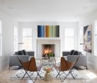 Modern art and a textured rug in a living room with a fireplace