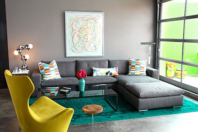 modern living room with a green overdyed rug bold red and orange rugs