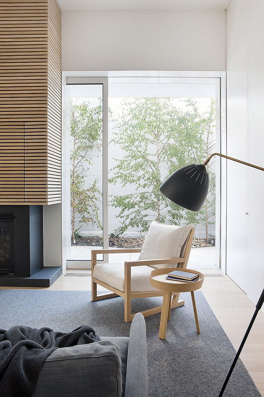 Reading spot next to the fireplace with pale timber chair