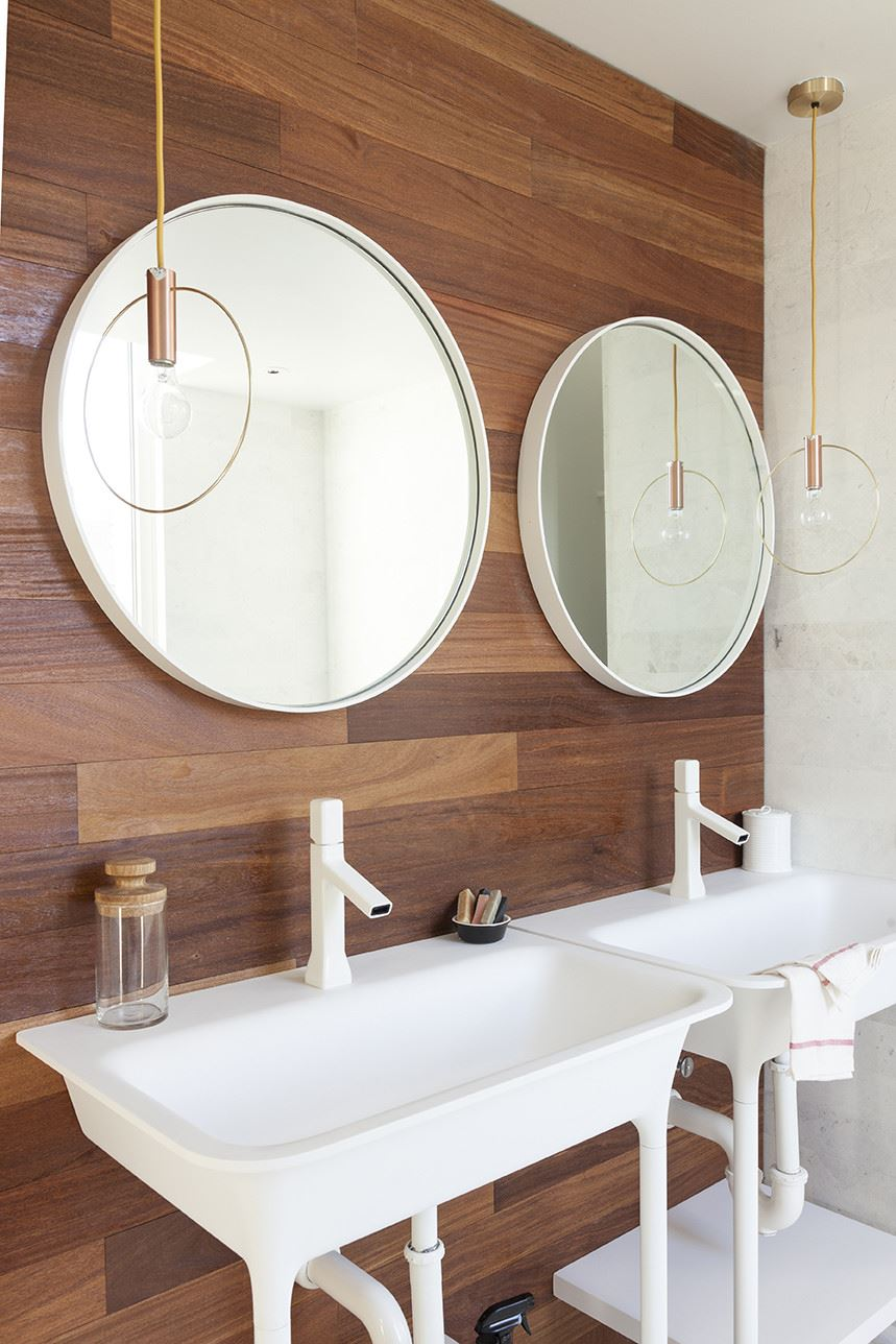 Round mirrors and pendant lighting in a modern bathroom
