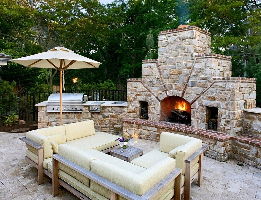 Stone fireplace next to the outdoor kitchen and a lovely lounge [By: Bruce Palmer Coastal Design]