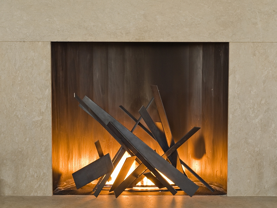 Tapering steel plates inside the fireplace bring geometric style to the room