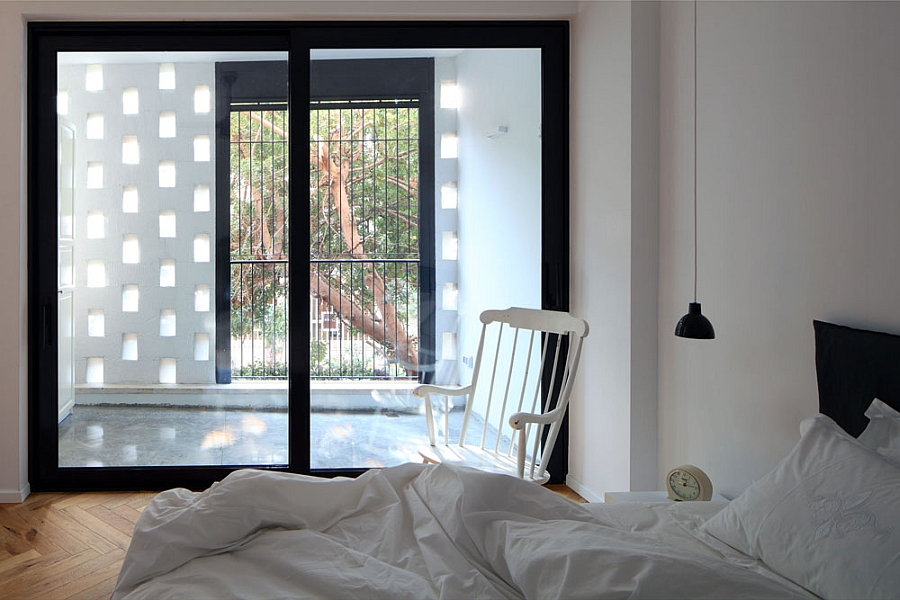 Brick wall and glass window usher in ample ventilation into the bedroom