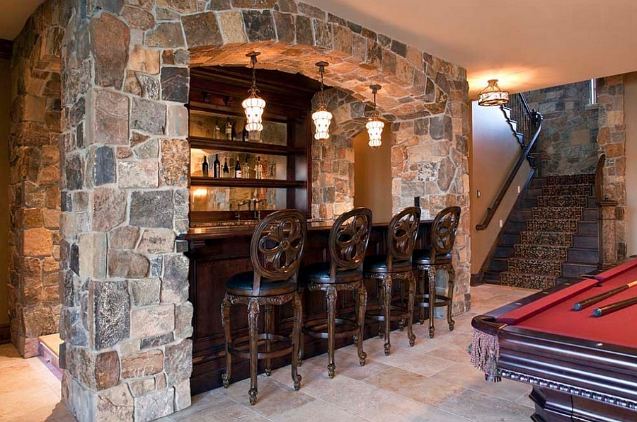 Classic basement bar design with a pool table next to it [Design: Hendel Homes]