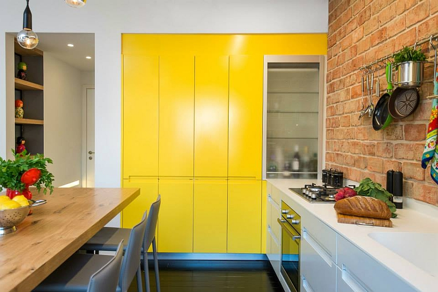 Small L-shaped kitchen in yellow and white with ample storage