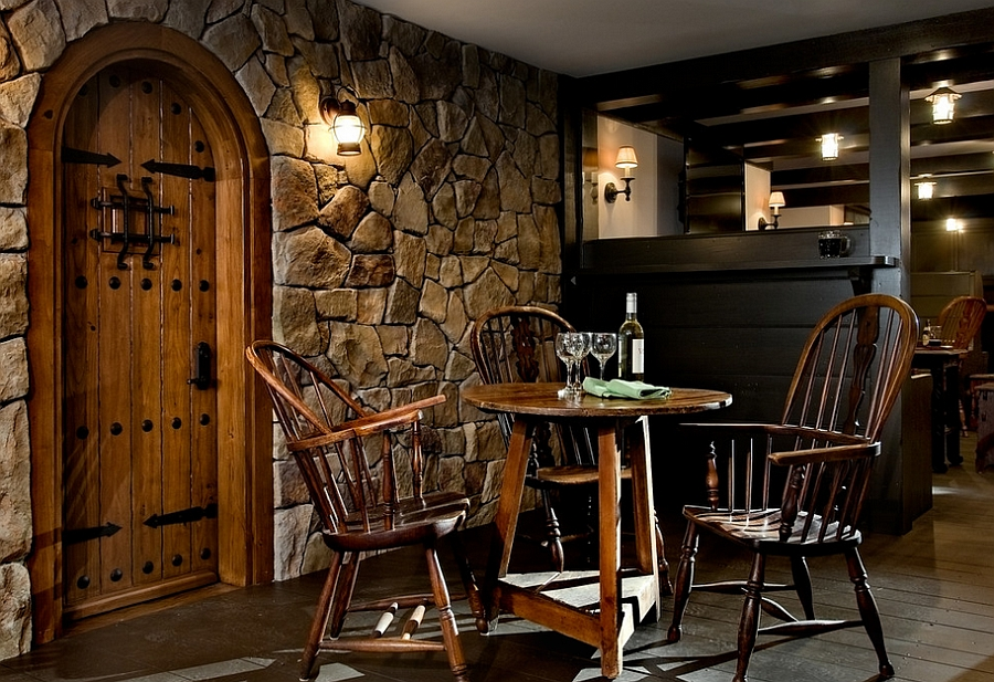 Stone wall and iron detailing give the basement makeover an authentic feel [Design: Crisp Architects]