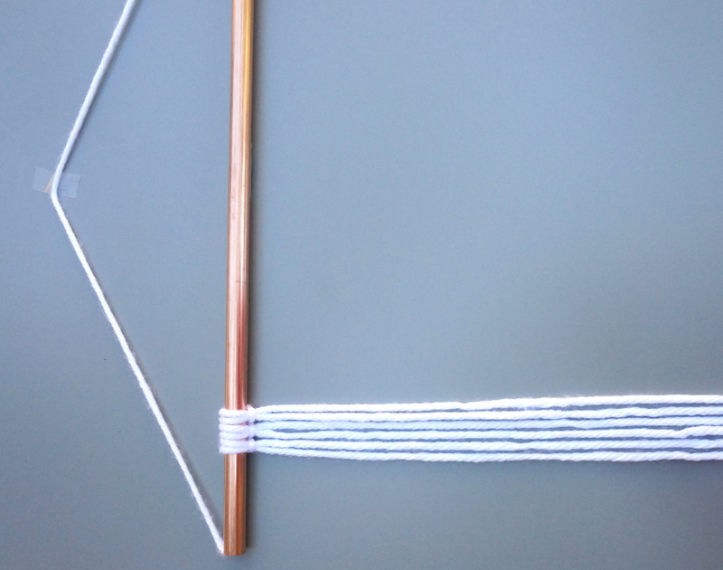 Tying yarn to the copper pipe begins the wall hanging