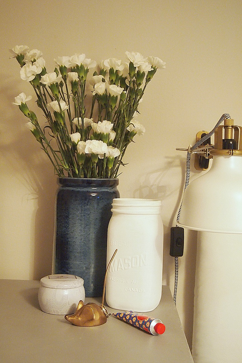 White mason jar styled on nightstand
