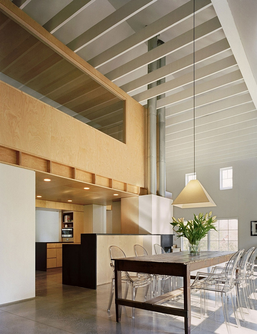 Acrylic chairs at the dining table add to the airy appeal of the loft-like barn house
