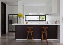 Dark kitchen island brings visual contrast to the white kitchen