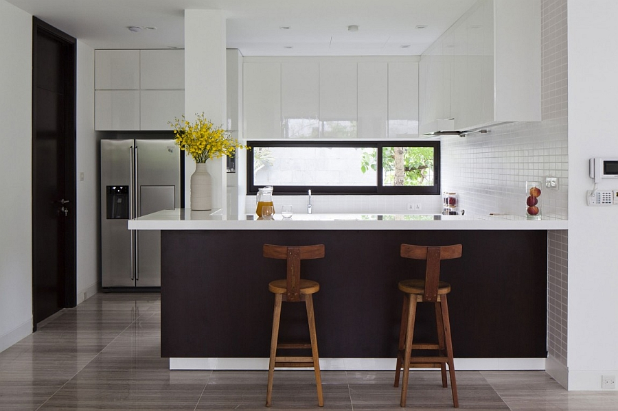 Dark kitchen island brings visual contrast to the white kitchen