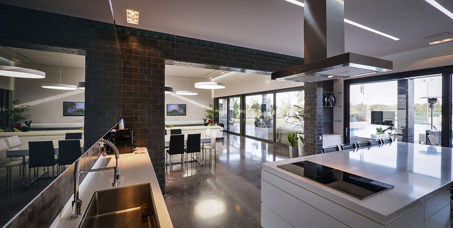 Dark kitchen walls and white countertops create a posh space