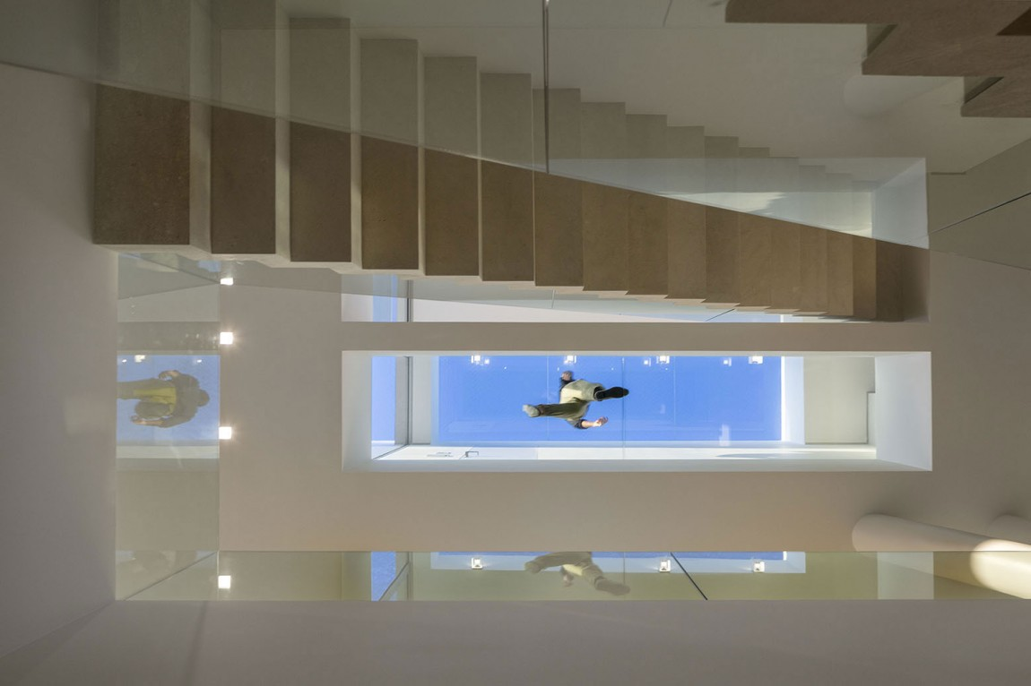 Glass walkway on the top floor viewed from the ground level of the house