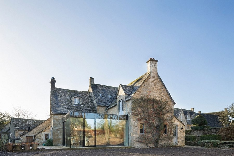 Lovely glass extension reflects the garden landscape outside during daytime