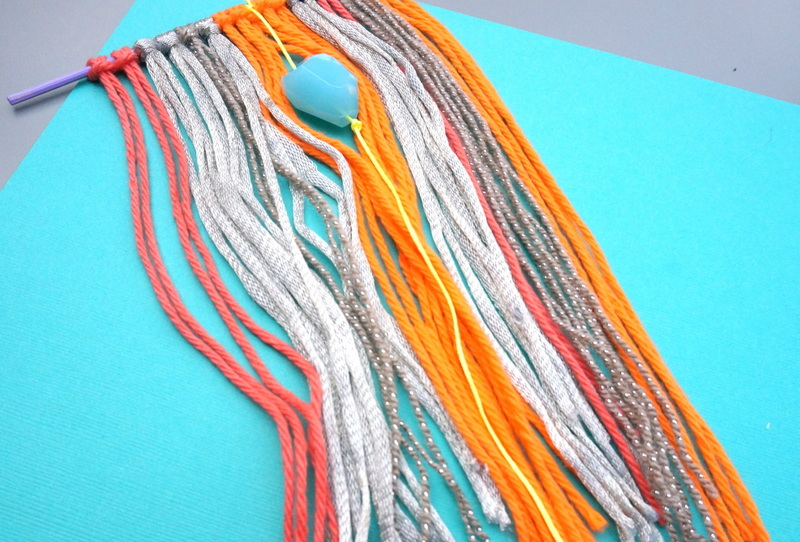 Orange and tan wall hanging with a turquoise mineral