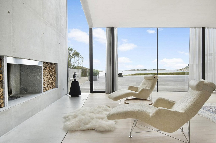 Plush chairs and rug next to the fireplace with a view of the sea