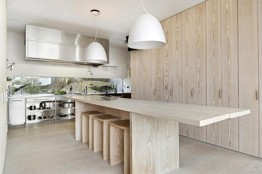 Raw wooden textures and bold pendants create the minimalist kitchen