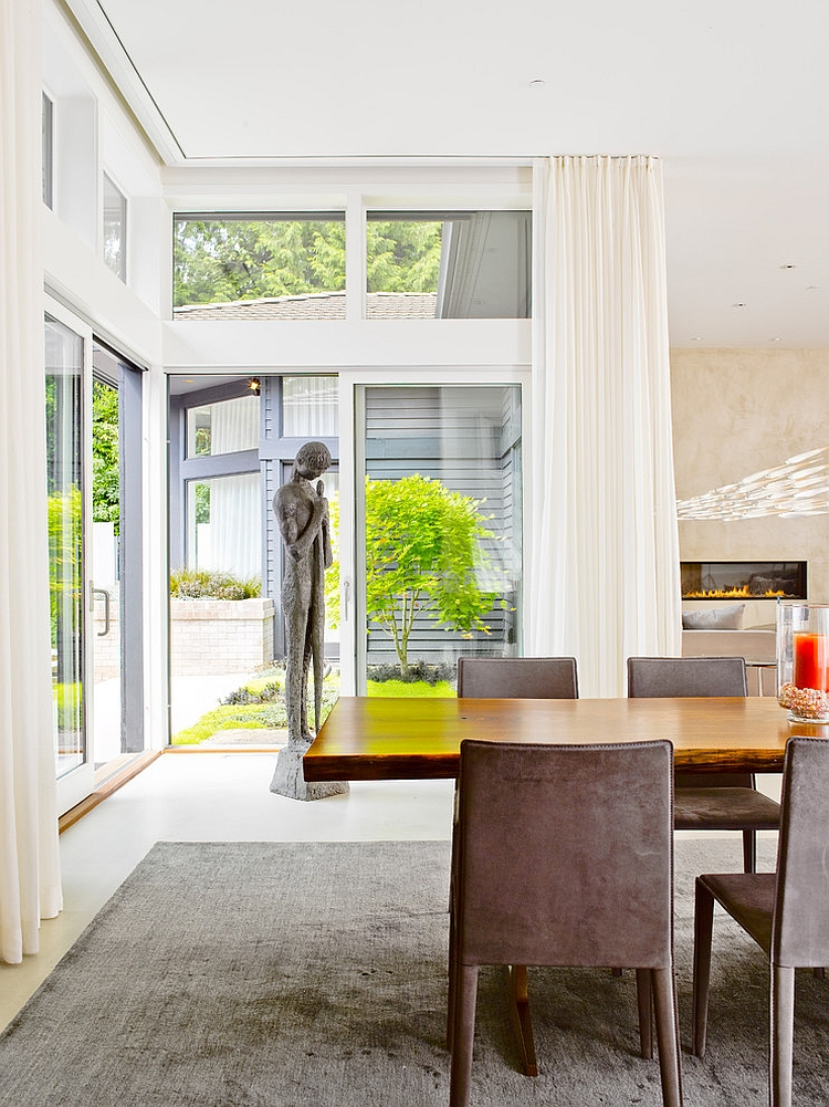 Sculptural addition in the corner and glass walls add elegance to the contemporary dining room