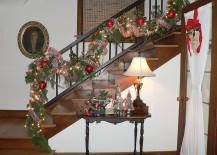 Shiny Christmas ornaments and strings lights used to decorate the staircase