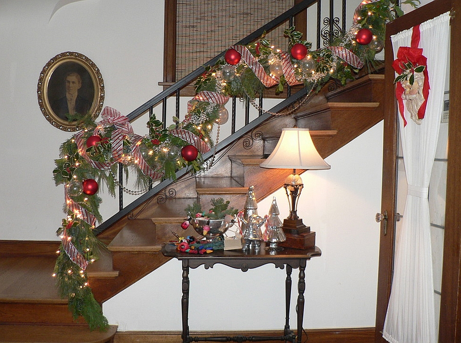 Shiny Christmas ornaments and strings lights used to decorate the staircase [Design: Timothy De Clue Design]