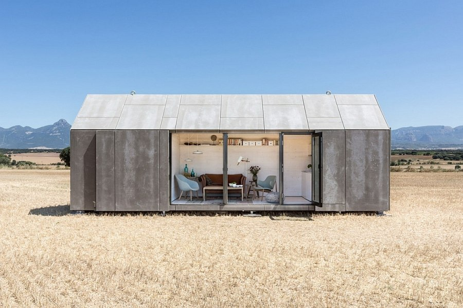 Sliding cement panels and glass doors connect the small portable house with outdoors