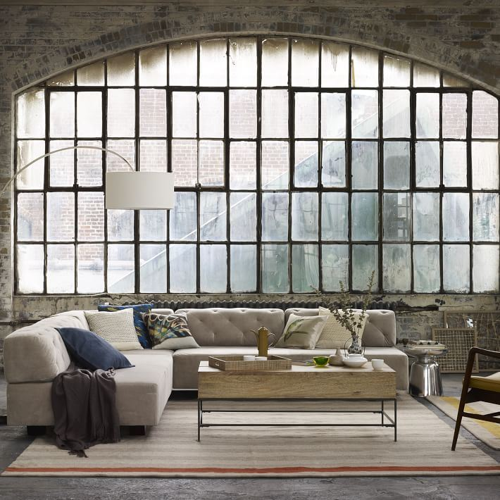 Tufted sectional sofa in a warehouse-style space