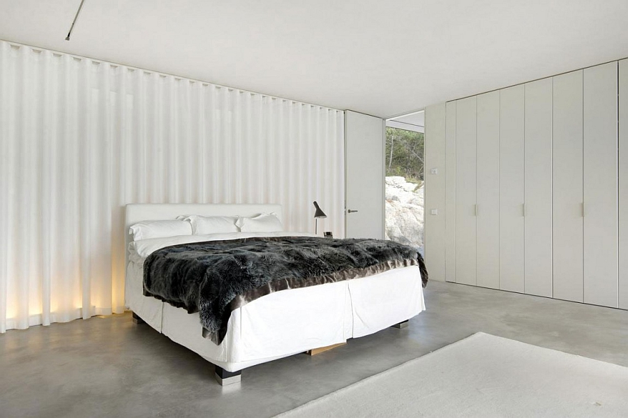 White sheer curtains bring a touch of softness to the minimal bedroom