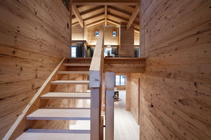 Wooden staircase inside the chalet leading to the top level