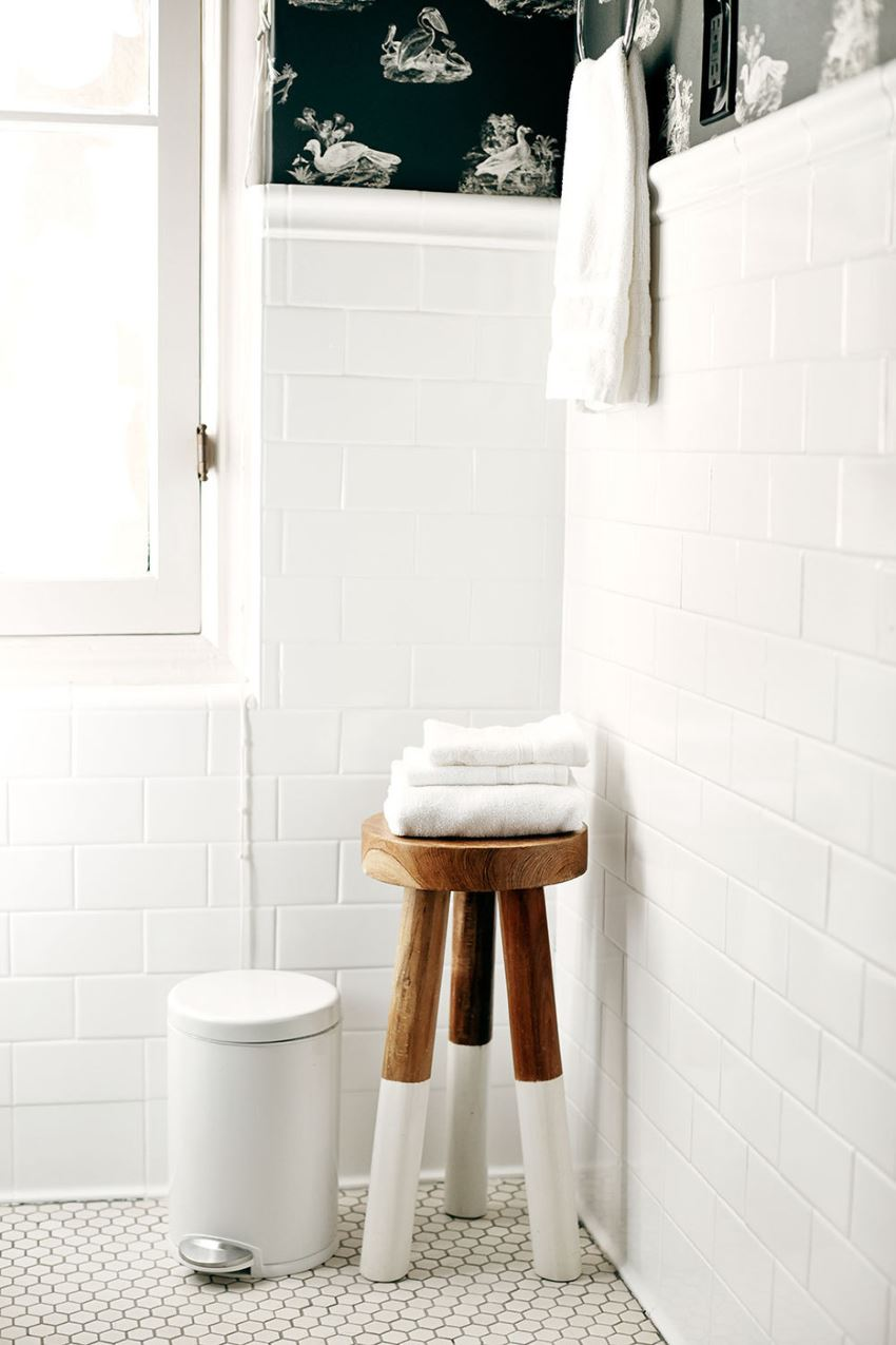 Wooden stool filled with towels 10 Modern Bathroom Spaces with Cozy Features