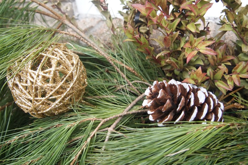 white painted pine cone with greenery