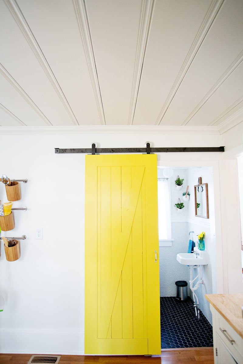 A sliding yellow barn door from A Beautiful Mess