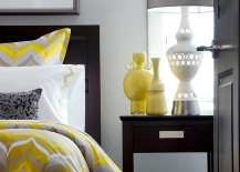 Bedding and vases add pops of yellow to the gray bedroom