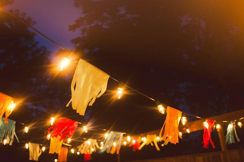 Colorful flags hang above a summertime porch party