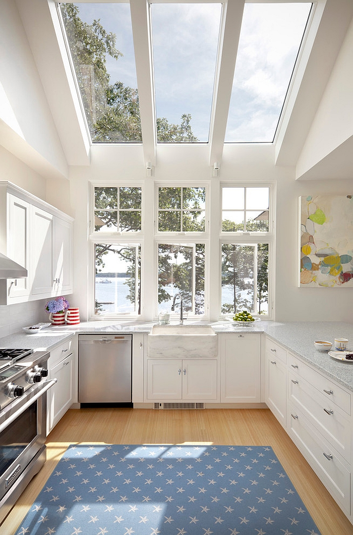Contemporary kitchen in white opens up towards the view outside [Design: Knickerbocker Group]