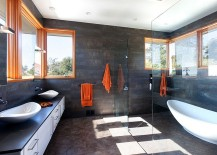Dark bathroom walls offer the ideal background for the orange accents