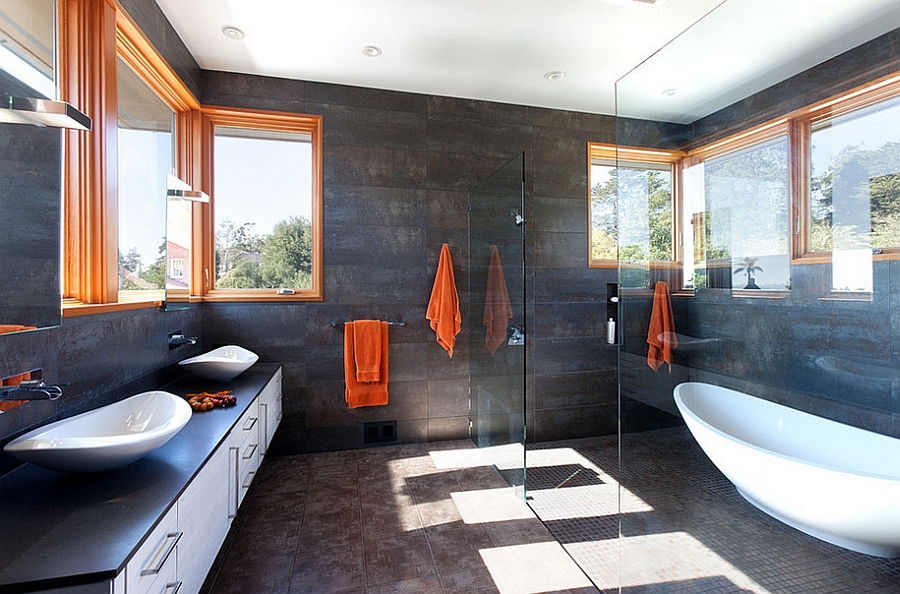 Dark bathroom walls offer the ideal background for the orange accents [Design: Dotter & Solfjeld Architecture + Design]