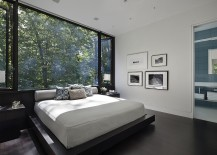 Exquisite bedroom uses large glass windows to offer unabated views of the forest outside