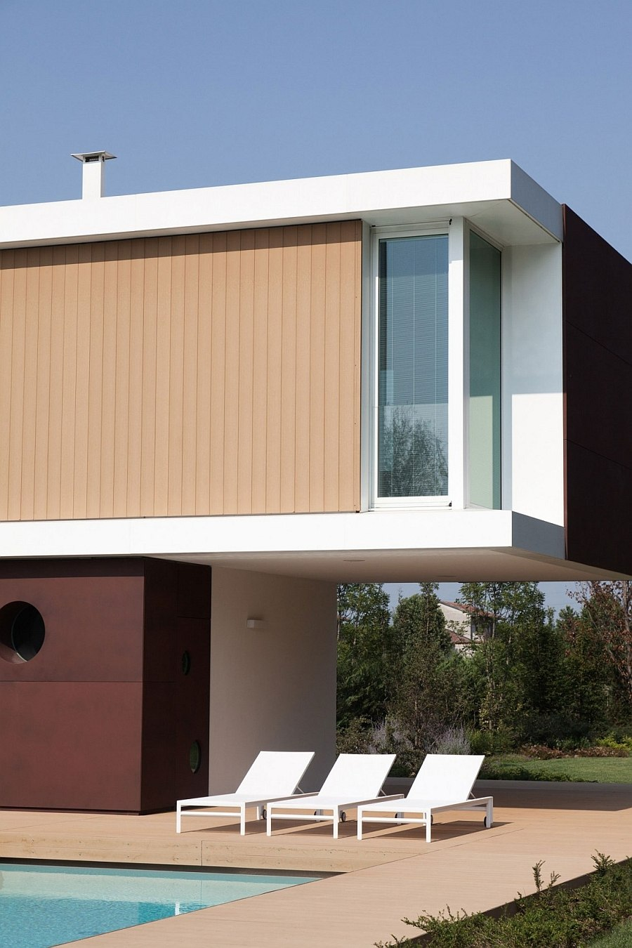 Exterior clad in white stucco, corten steel and wooden slats