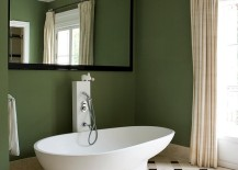 Green backdrop in the bathroom lets the white freestanding bathtub standout