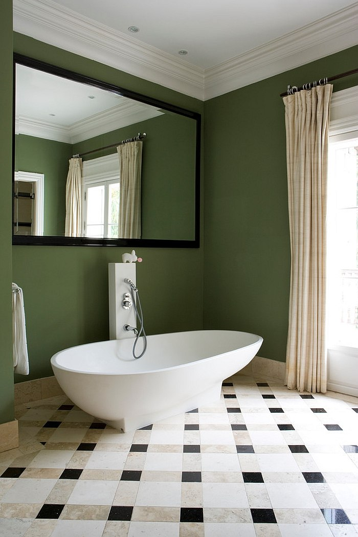 Green backdrop in the bathroom lets the white freestanding bathtub standout [Design: Luis Pons Design Lab]