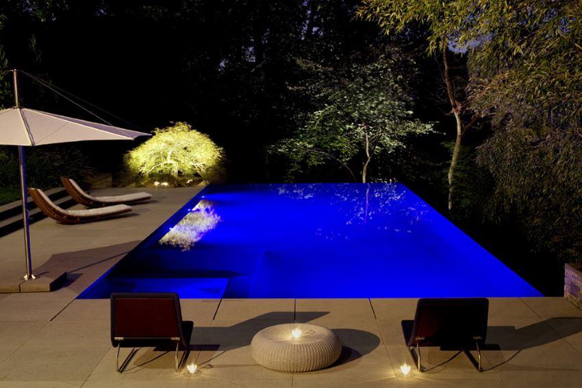 Lit tree near a modern pool