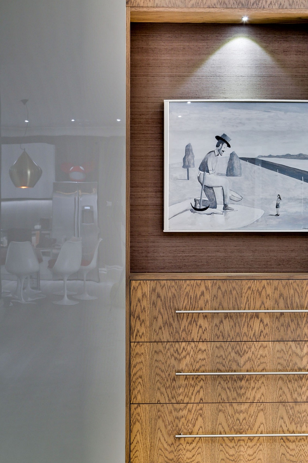 Lovely artwork and wooden divider storage add visual contrast to the posh bachelor pad
