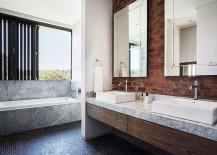 Modern bathroom with marble bathtub and a brick wall