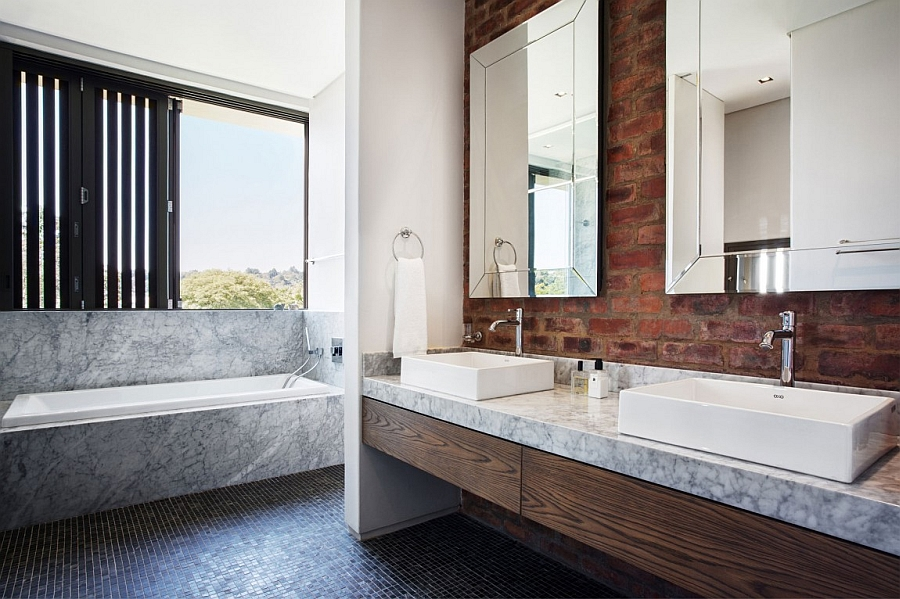 Modern bathroom with marble bathtub and a brick wall