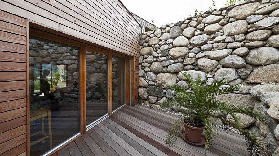 Natural stone wall of the house gives the facade textural contrast